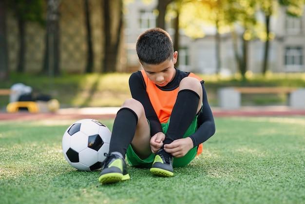 Jogador de futebol adolescente no campo de esporte ao ar livre, amarrando o cadarço nas botas.