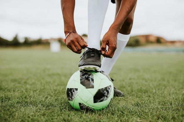 Jogador de futebol amarrando o cadarço