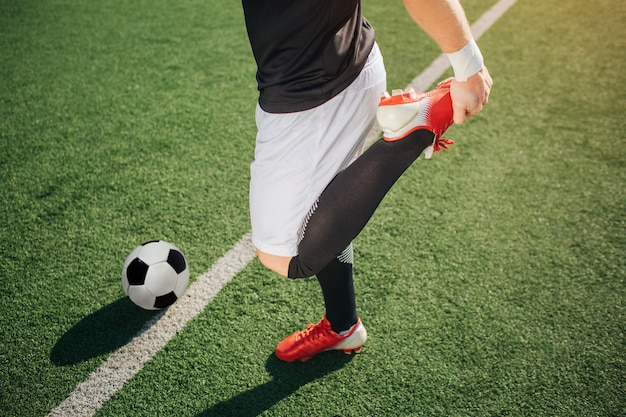 Jogador de futebol americano aquecendo a perna