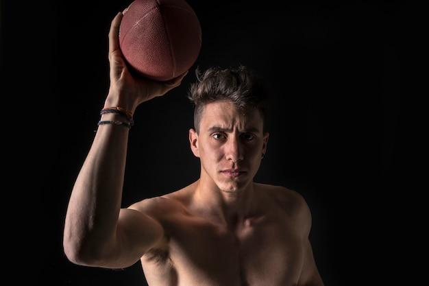 Jogador de futebol americano com abs no preto