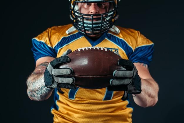 Jogador de futebol americano com bola atada nas mãos