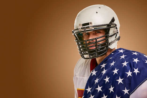 Jogador de futebol americano com uniforme e bandeira americana, orgulhosa de seu país, em um branco