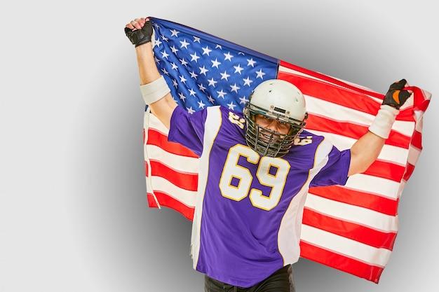 Jogador de futebol americano com uniforme e bandeira americana, orgulhosa de seu país, em uma parede branca