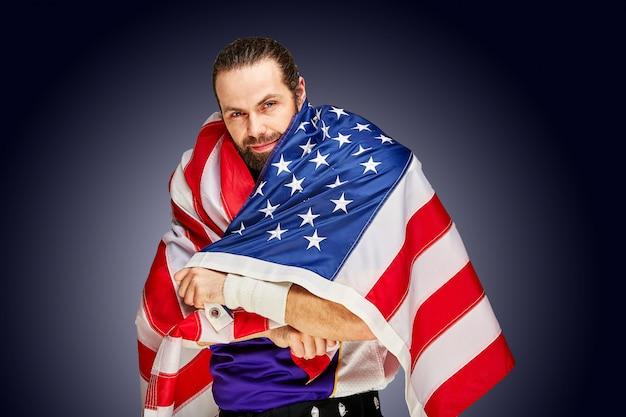 Jogador de futebol americano com uniforme e bandeira americana orgulhosa de seu país, sobre um fundo branco.