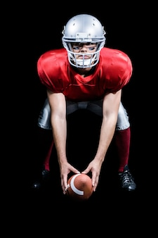 Jogador de futebol americano, dobrando-se enquanto segura a bola
