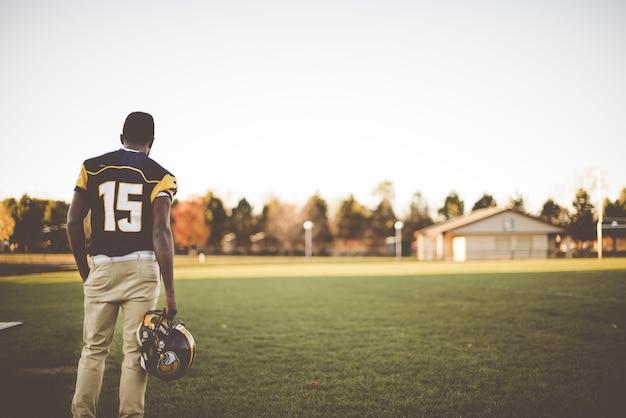 Jogador de futebol americano em pé no campo se preparando para a partida