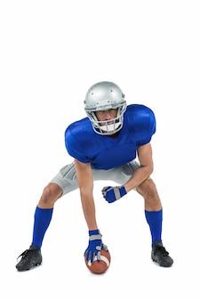 Jogador de futebol americano em posição de ataque