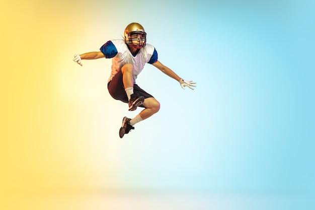 Jogador de futebol americano isolado na superfície do estúdio gradiente em luz de néon