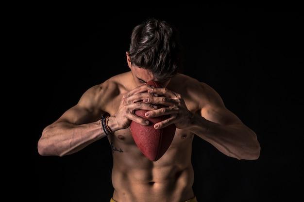 Jogador de futebol americano nu com abs no preto
