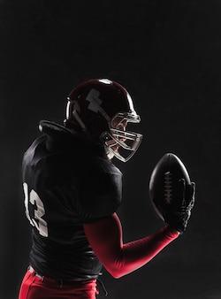 Jogador de futebol americano posando com bola na parede preta