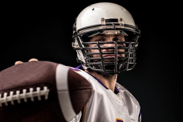 Jogador de futebol americano segurando a bola nas mãos na frente da câmera