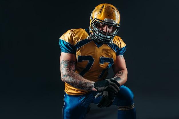 Jogador de futebol americano segurando a bola nas mãos