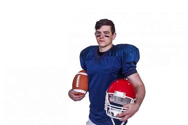 Jogador de futebol americano segurando uma bola e capacete