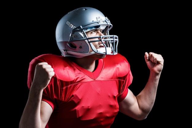 Jogador de futebol americano, torcendo com o punho cerrado