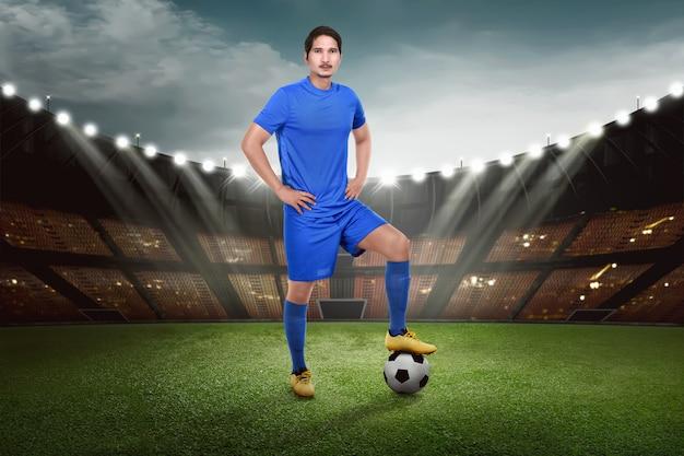Jogador de futebol asiático atraente com bola