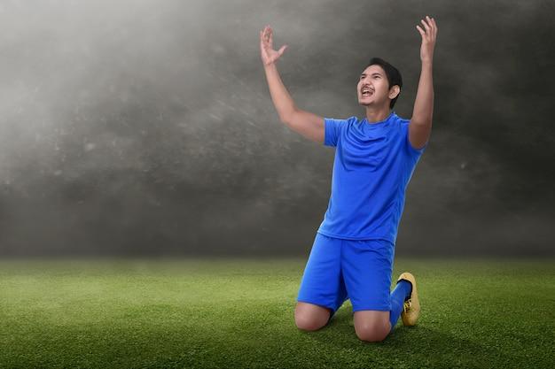 Jogador de futebol asiático atraente comemorar sua vitória