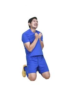 Jogador de futebol asiático profissional com camisa azul comemorando