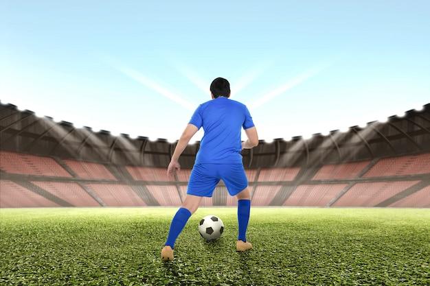 Jogador de futebol asiático profissional driblando a bola