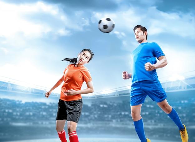 Jogador de futebol asiático pular e duelo, dirigindo a bola no ar no campo de futebol