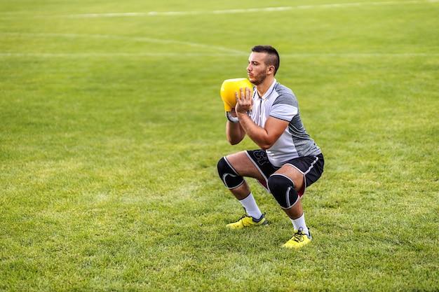 Jogador de futebol atraente dedicado em forma, fazendo resistência de agachamento com sino de chaleira.
