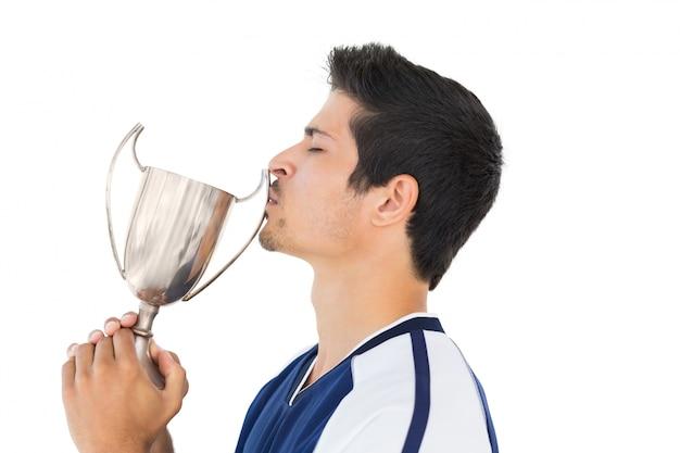 Jogador de futebol beijando o copo dos vencedores