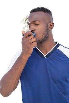 Jogador de futebol beijando vencedores troféu sobre fundo branco