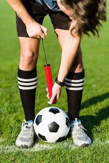 Jogador de futebol bombeando bola de futebol
