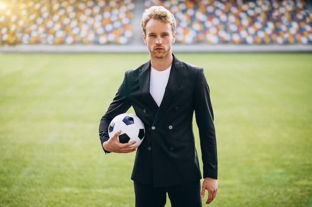 Jogador de futebol bonito no estádio em terno de negócio
