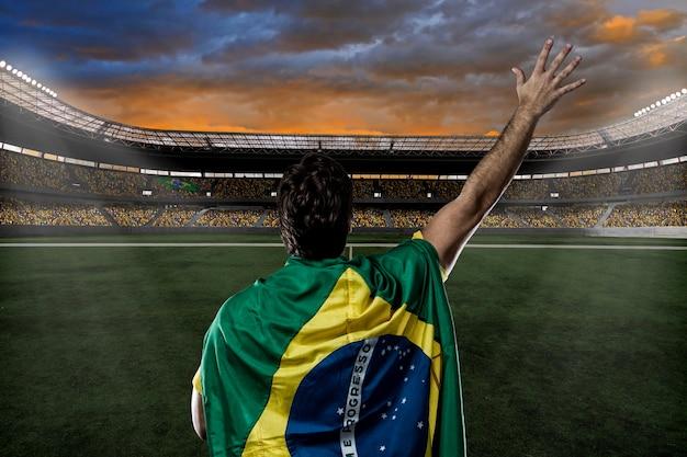 Jogador de futebol brasileiro com a bandeira do brasil nas costas, comemorando com a torcida.