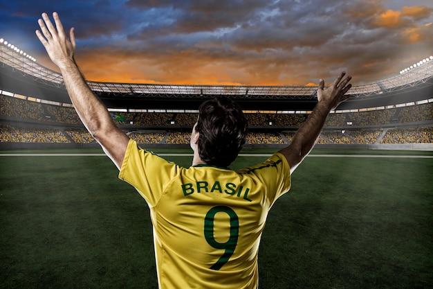 Jogador de futebol brasileiro, comemorando com a torcida.