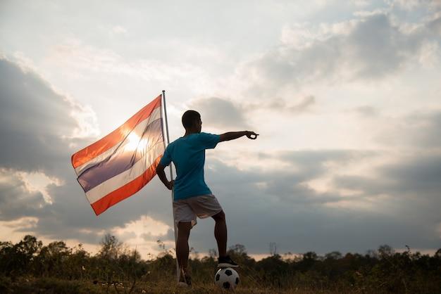 Jogador de futebol brasileiro, segurando a bandeira da tailândia