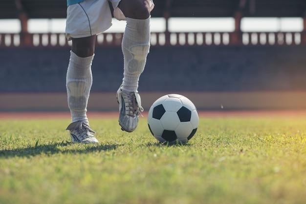Jogador de futebol chuta a bola no estádio de futebol