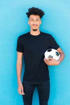 Jogador de futebol com bola debaixo do braço perto da parede