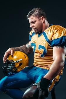 Jogador de futebol com bola e capacete nas mãos