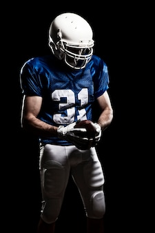 Jogador de futebol com número em um uniforme azul e uma bola na mão.