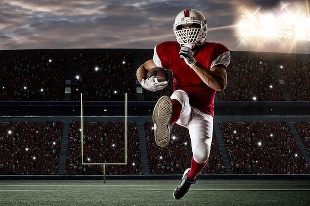 Jogador de futebol com um uniforme vermelho correndo em um estádio.