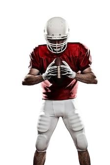 Jogador de futebol com um uniforme vermelho e uma bola na mão em um espaço em branco.