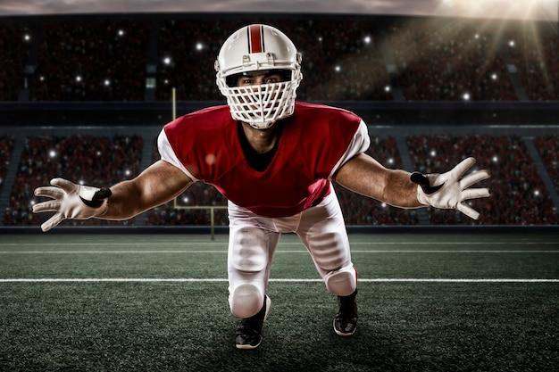 Jogador de futebol com um uniforme vermelho, fazendo um tackle em um estádio.