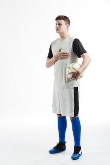 Jogador de futebol com uma mão no peito