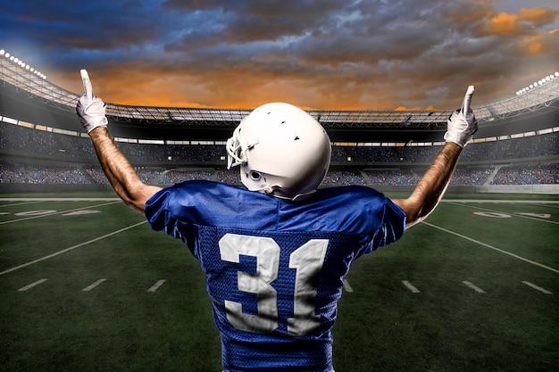 Jogador de futebol com uniforme azul comemorando com a torcida.