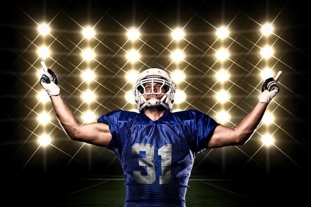 Jogador de futebol com uniforme azul comemorando na frente das luzes