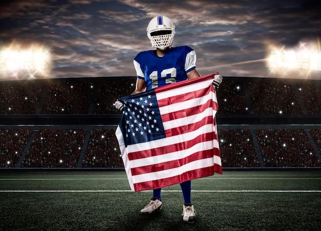 Jogador de futebol com uniforme azul e bandeira americana, em estádio