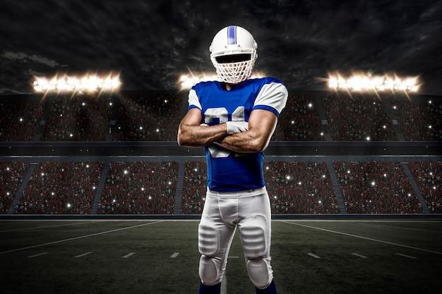 Jogador de futebol com uniforme azul em estádio