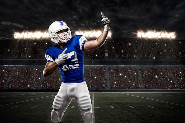 Jogador de futebol com uniforme azul fazendo selfie em um estádio