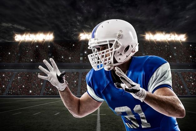 Jogador de futebol com uniforme azul fazendo um tackle em um estádio