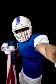 Jogador de futebol com uniforme azul fazendo uma selfie em uma parede preta