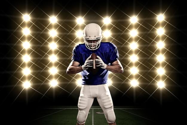 Jogador de futebol com uniforme azul na frente das luzes