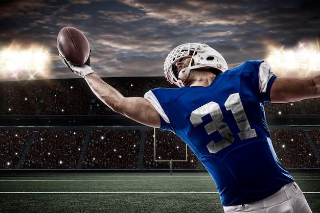 Jogador de futebol com uniforme azul pegando uma bola em um estádio