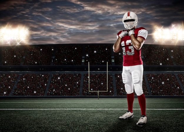 Jogador de futebol com uniforme vermelho em um estádio.