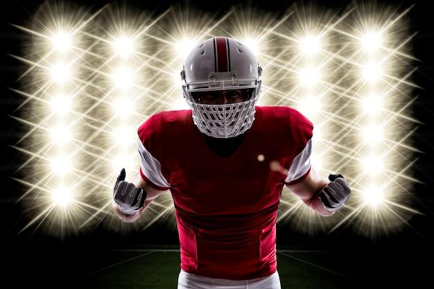 Jogador de futebol com uniforme vermelho na frente das luzes.